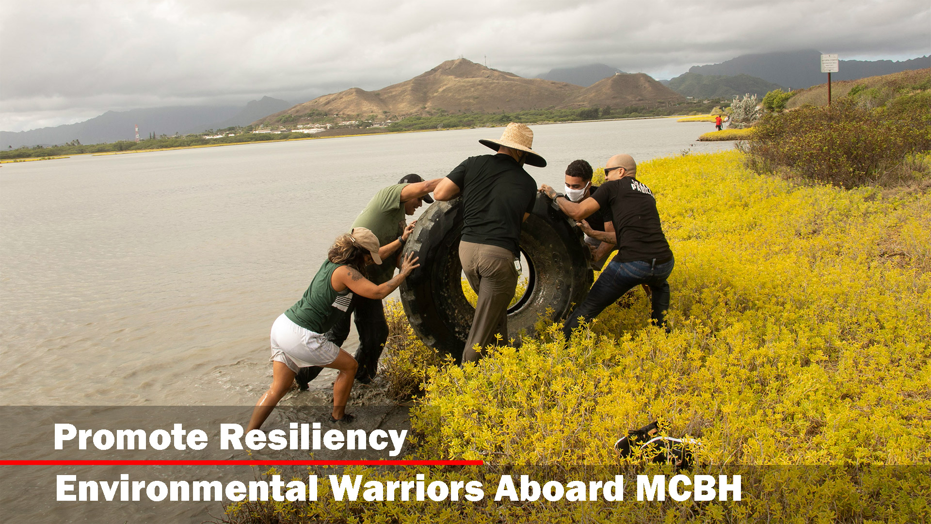 Volunteers push a tire out of the water during a Weed Warriors event aboard Marine Corps Base Hawaii